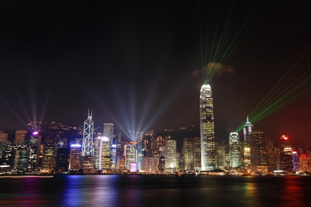 Hong Kong skyline at night with lights show and skyscrapers over sea with laser beams photo