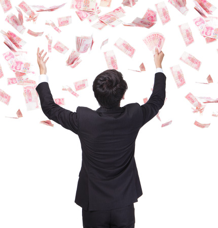 happy business man hold China money ( Renminbi ) under a money rain - isolated over a white background, asian model photo