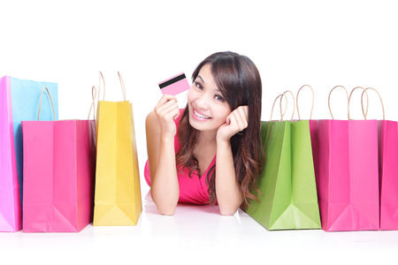 gift bag: Portrait of a young girl lying with shopping bags and show credit card isolated on white , asian beauty Stock Photo