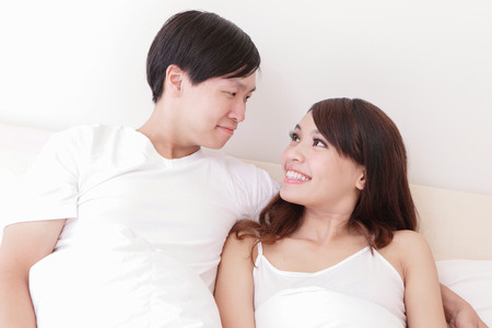young lovely couple lying in a bed, happy smile looking to each other, asian people