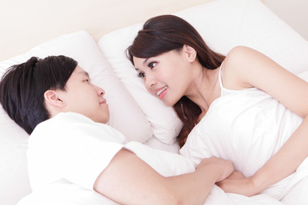 young lovely couple lying in a bed, happy smile looking to each other, asian people photo