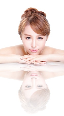 Beautiful face skincare beauty woman lying down with mirror reflection isolated on white background. asian beauty model photo