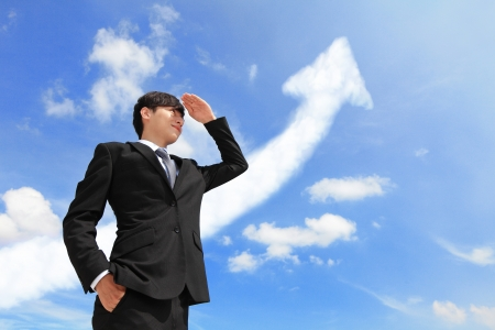 Successful handsome business man purposefully looking away with arrow cloud and blue sky, model is a asian male photo