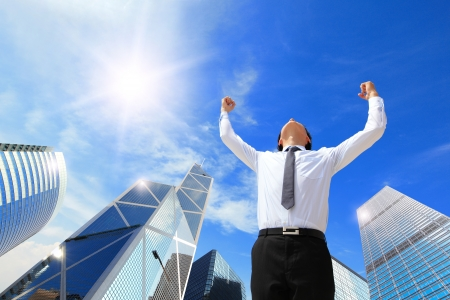 happy successful business man raised arms with sky in the background, asian people