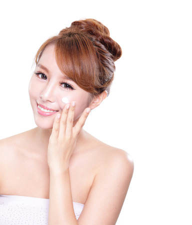 cheek to cheek: Portrait of young woman applying moisturizer cream on her pretty face isolated on white background, asian beauty
