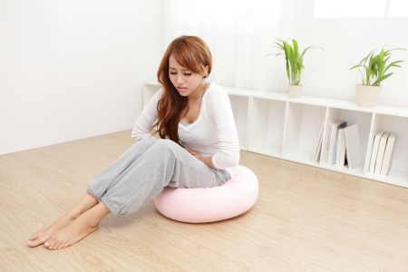 periods: Portrait of woman with stomach ache sitting on floor at home, asian model Stock Photo