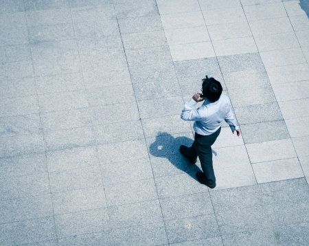 successful business: blur business man walking and using smart phone on the street