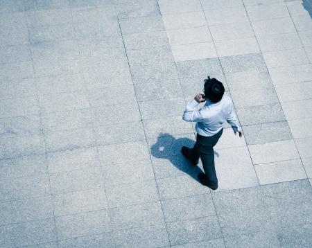 personnes qui marchent: flou homme d'affaires marchant et en utilisant t�l�phone intelligent dans la rue