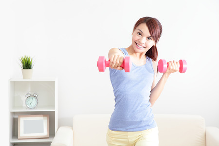 indoors: beautiful sporty woman working out with two dumbbells , asian beauty model
