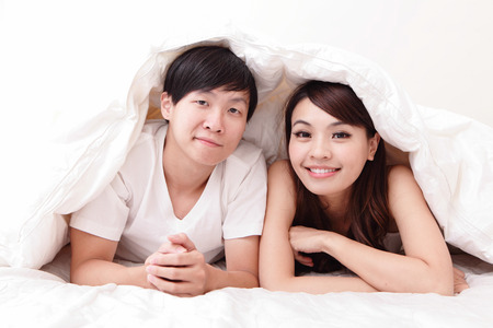 happy asian couple: young lovely couple lying in a bed, happy smile looking to camera, asian people