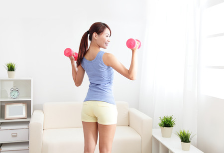 beautiful sporty woman working out with two dumbbells , asian beauty model photo