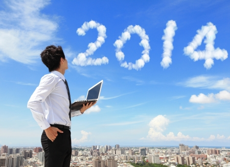 cloud computing concept: Young business man using laptop and look to 2014 year text with blue sky and cloud and cityscape in the background, business and cloud computing concept
