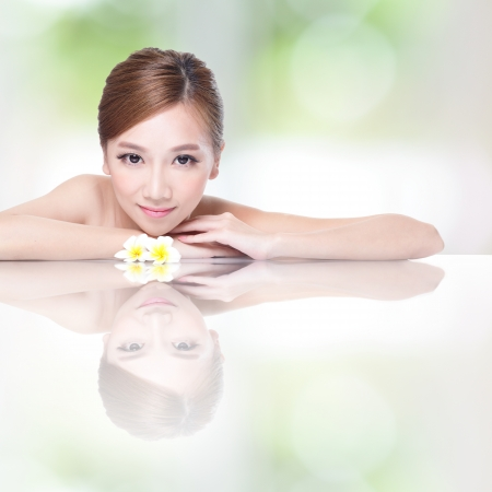 Beautiful face beauty woman lying down with flower amd mirror reflection. SPA concept, asian beauty photo