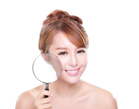 problema: Mujer joven con la piel perfecta y lupa comprobar que el aislado en el fondo blanco, el concepto de cuidado de la piel Foto de archivo