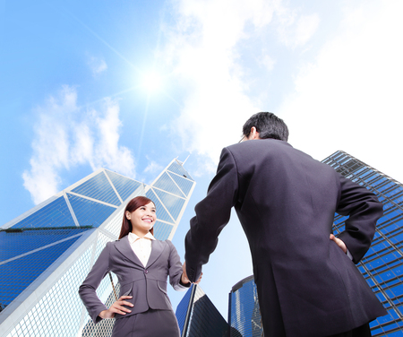 handshake business: Business woman and man handshake with business office building background, asian, hong kong Stock Photo