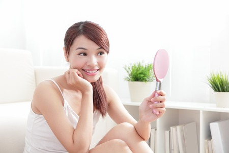 Woman caring of her beautiful skin and face by mirror at home, asian beauty photo