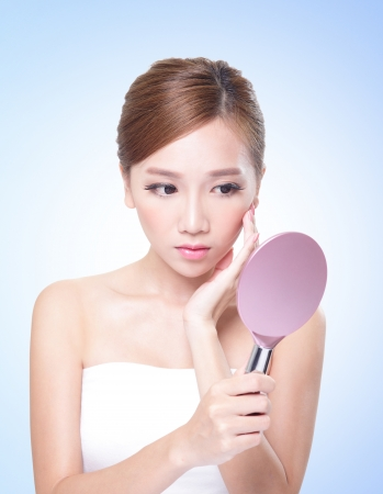 Skin Care Woman Looking At Herself In The Mirror isolated on blue background, asian beauty photo