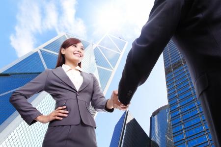 boss: Mujer de negocios y hombre apretón de manos con el edificio de oficinas de negocios