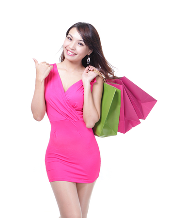 asian model: happy shopping young woman show thumb up with bags - isolated on white background, asian model Stock Photo
