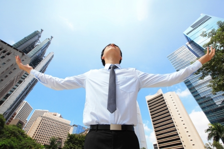outstretch: carefree business man arms up and looking to empty copy space with business building background, asian model, hong kong Stock Photo
