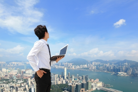 Young business man using laptop and look to cityscape, asian, hong kong photo