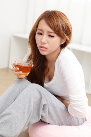 dolor de estomago: Retrato de mujer con dolor de est�mago sentado en el suelo en casa, modelo asi�tico