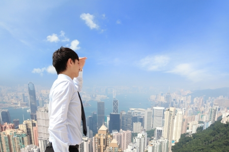 Successful business man looking away with city background, asian, hong kong photo