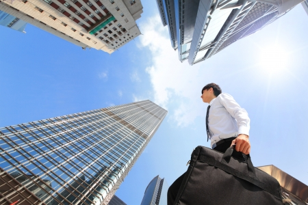 briefcase: happy successful business man outdoors Next to Office Buildings with cityscape and sky, hong kong, asia, asian