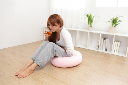 stomach: Portrait of woman with stomach ache sitting on floor at home, asian model Stock Photo