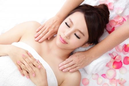 shoulders: Beautiful woman smile getting massage and spa treatment on shoulder with rose, asian beauty