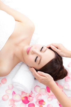 tratamientos corporales: Hermosa mujer joven disfrutar de la recepci�n masaje facial en el spa con rosas en el fondo, ella es muy relajada (primer plano), el modelo es una belleza asi�tica