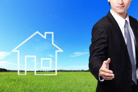 businessman handshake, welcome gesture, with New house imagination vision on green meadow. Real estate Concept photo