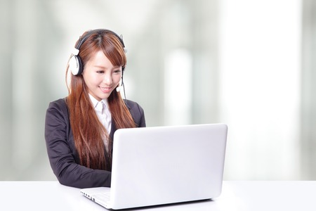 female in suit typing on her laptop and using headphones while sitting in an office photo