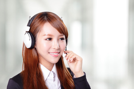 Portrait of happy smiling support phone operator in headset, asian