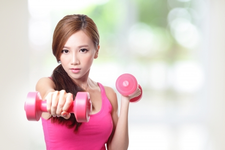 Young sport girl with dumbbells with green background, asian Stock Photo