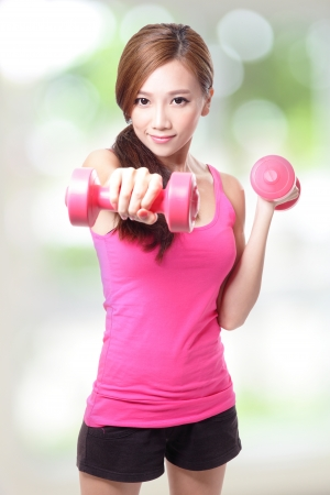 asian bodybuilder: Young sport girl with dumbbells with green background, asian Stock Photo
