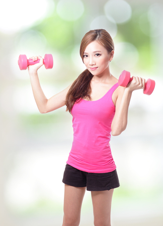 gymnastics equipment: Young sport girl with dumbbells with green background, asian Stock Photo