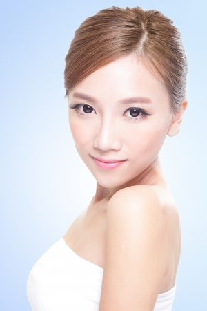 Beautiful young adult woman with clean fresh face, blue background, asian photo