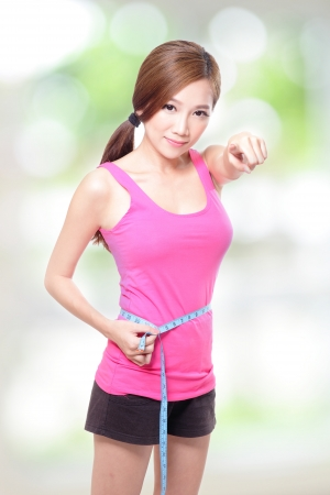 sporty woman shapes and measure on green background, asian photo