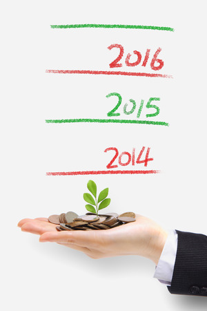 christmas profits: new green plant sprouting from a hand with money with 2014 new year ,concept for business, growth and money
