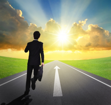 business man running forward on asphalt road with arrow , and beautiful sunset and sunshine, business concept