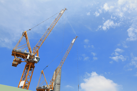 heavy lifting: Tower Cranes and construction with blue sky