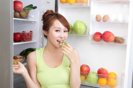 icebox: Healthy Eating Concept .Diet. Beautiful Young Woman eat kiwi fruit near the Refrigerator with healthy food. Fruits and Vegetables, asian model