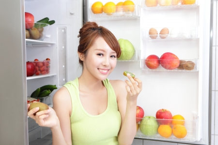 Healthy Eating Concept .Diet. Beautiful Young Woman eat kiwi fruit near the Refrigerator with healthy food. Fruits and Vegetables, asian model photo