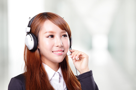 Portrait of happy smiling support phone operator in headset, asian photo