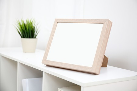 indoor photo: blank photo frame with copy space on white bookshelf at home