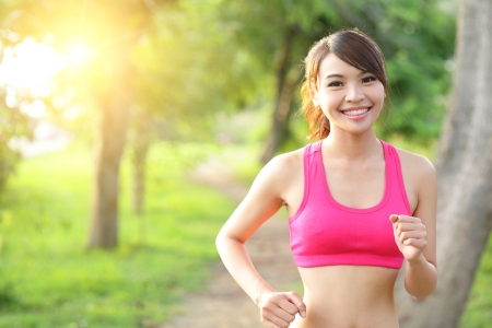 asian trees: Running woman in park. Asian sport fitness model in sporty running clothes.