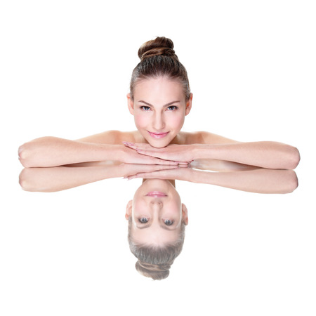 Beautiful face skincare beauty woman lying down with mirror reflection isolated on white background. photo