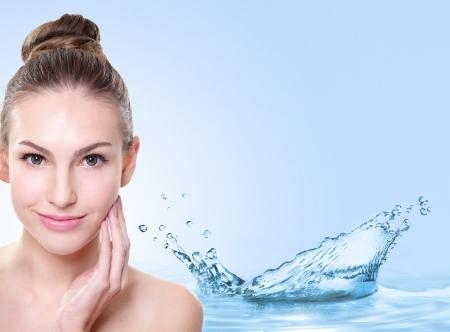 agua: Concepto de la belleza del cuidado de piel, la cara hermosa de la mujer con las salpicaduras de agua aisladas sobre fondo azul, modelo asiático