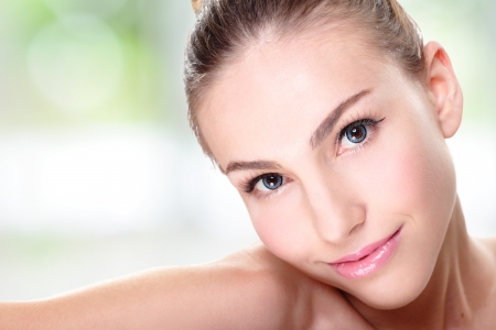Close up portrait of beautiful young woman face while lying. Isolated on green background. Skin care or spa concept photo